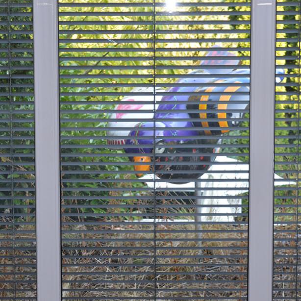 Das Foto zeigt den Blick durch Raffstoren-Jalousien nach außen.