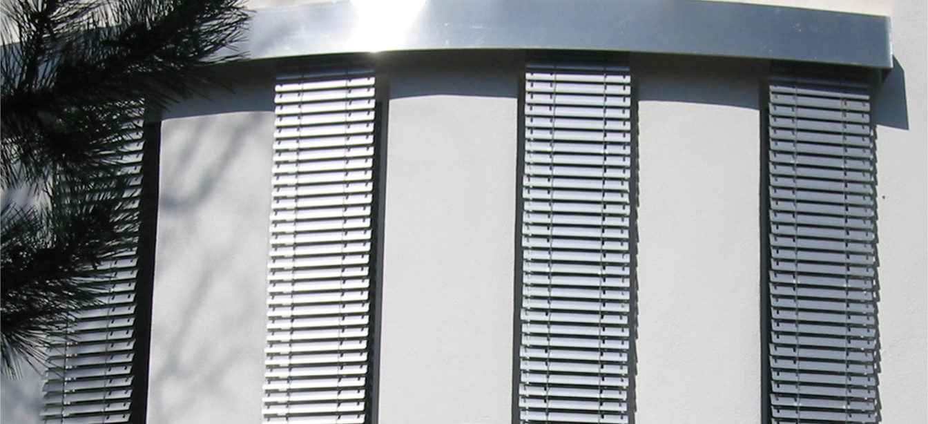 Das Bild zeigt schmale Jalousien an einem Haus aus der Nähe.
