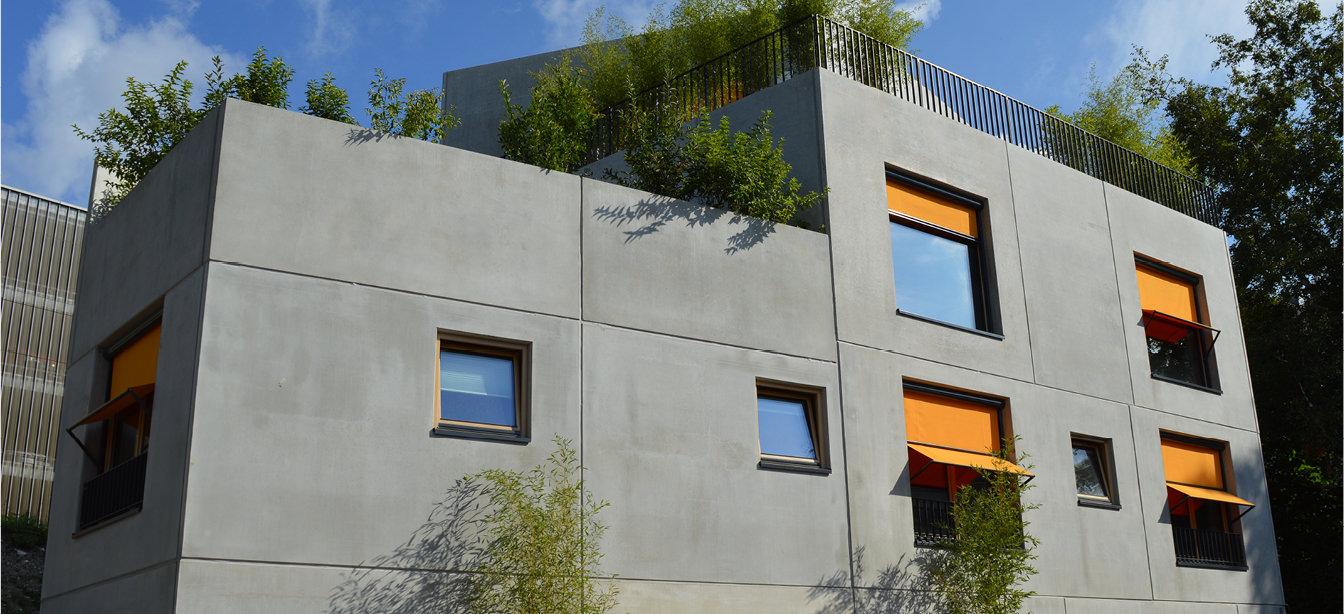 Hier sehen Sie Fassadenrollos als Senkrechtmarkise an einer Hausfassade.