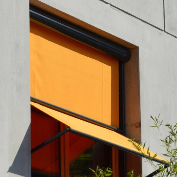 Das Foto zeigt orange Fassadenrollos als Senkrechtmarkise.